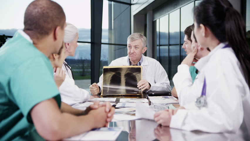 A diverse team of medical personnel are having a meeting in a light, modern private health care facility. They are discussing the x-ray of a patient's chest and looking for a diagnosis. #3848786