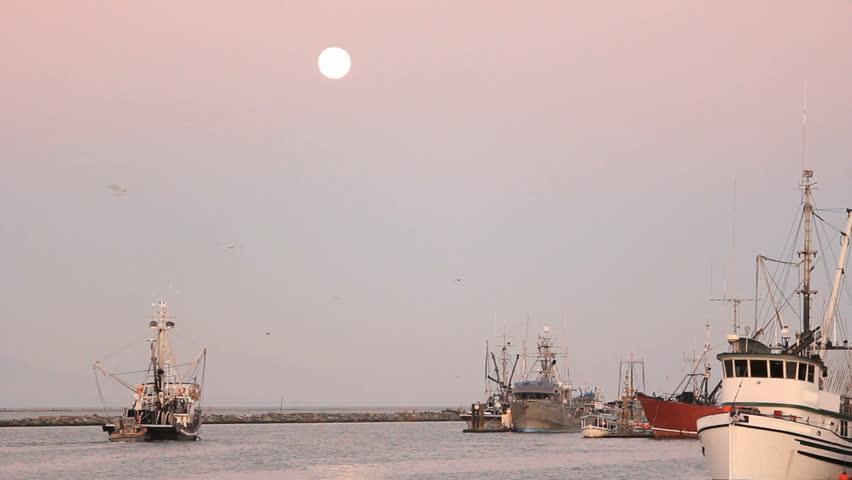 Full Moon, Steveston Harbor, Fishboat Departs. A fish boat departs Steveston Harbor on the Fraser River in British Columbia, Canada at sunrise as a full moon is setting.