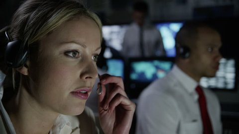 Two security workers in a busy system control room are taking calls via headsets and either issuing or receiving instructions.