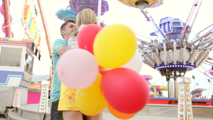 Joyful young couple visiting an amusement park arcade with man picking up girl with balloons and turning around smiling and having fun.