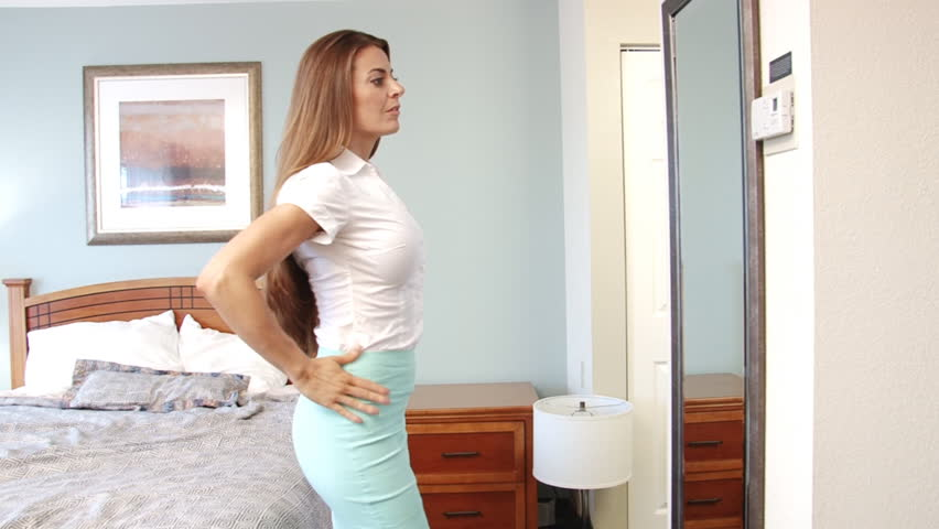 Sexy beautiful businesswoman looking at herself in mirror getting ready for work