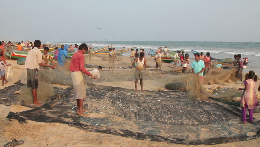 PURI, INDIA - FEBRUARY 2013: Fishermen dismantle net