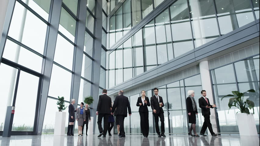 Diverse team of business people chat together as they walk around their light and modern office building.  | Shutterstock HD Video #3894359