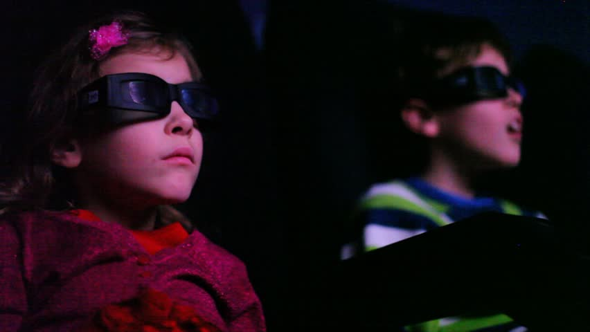Two kids in cinema watching a 3D movie, focus on girl