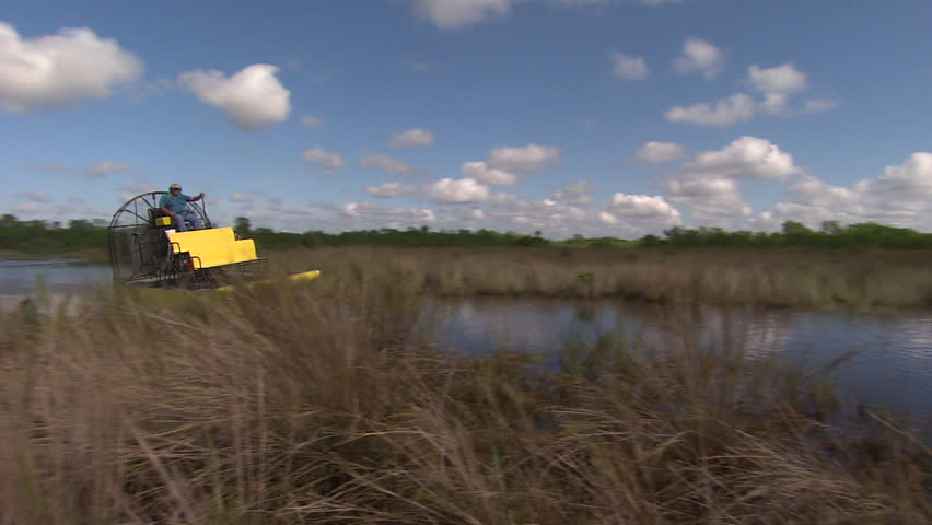 An air boat speeds toward the camera in the Florida everglades