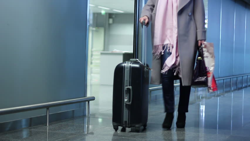 Woman with travel wheel bag coming out of airport arrival zone