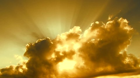 Beautiful yellow cloudscape with large, building clouds and sunrise breaking through cloud mass.