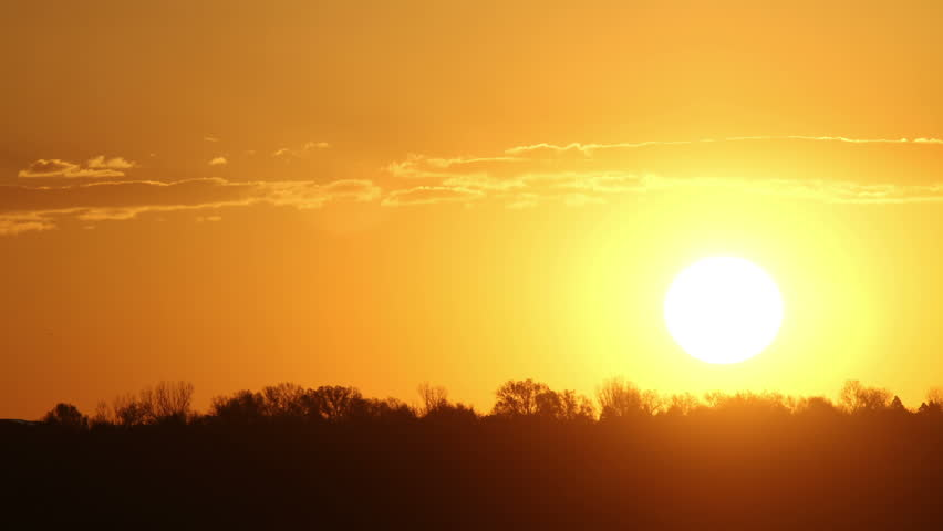 Red sun rises over the horizon, with a thin band of clouds. HD 1080p timelapse.