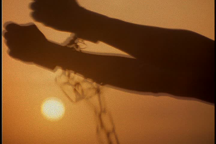 Slavery reenactment. CU silhouette of chained arms raised to the sun against a dark orange sky.