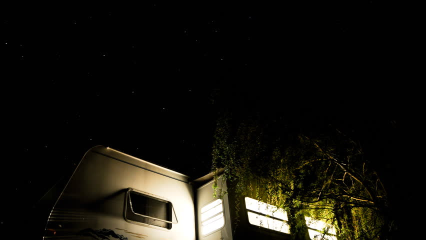 camper trailer sits under the stars as they go by and the lights go out (long)