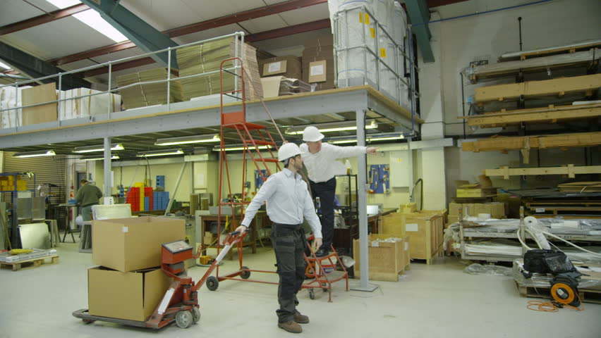 A  factory or warehouse worker who is moving boxes around is given instructions by an older, senior worker.
