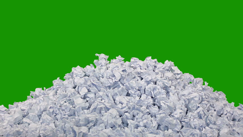 Green background (Chroma Key). New crumpled paper ball are added to the heap one