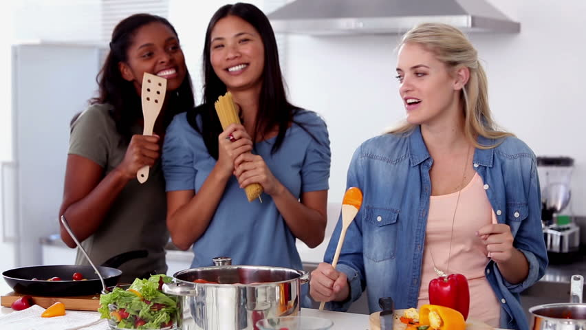 Laughing friends singing into a wooden spoon while cooking pasta in the kitchen