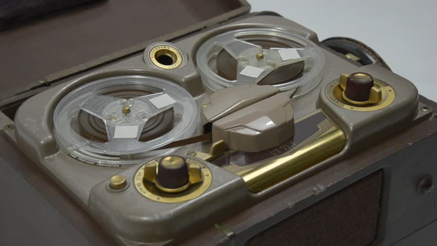 A hand starts and stops playing a tape on an old portable reel-to-reel tube recorder.