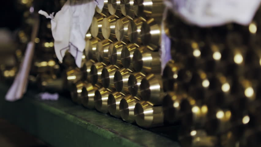 Stack of thick metal bars of brass in a factory warehouse