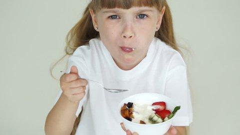 Little girl eating yogurt with fruit