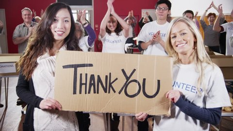 "Two attractive female charity volunteers of Caucasian and Asian ethnicity hold up a ""Thank You"" sign and smile into the camera. Their fellow volunteers applaud and cheer in the background.Slow motion."