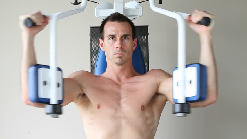 Hd topless adult male uses a chest exercising machine at a