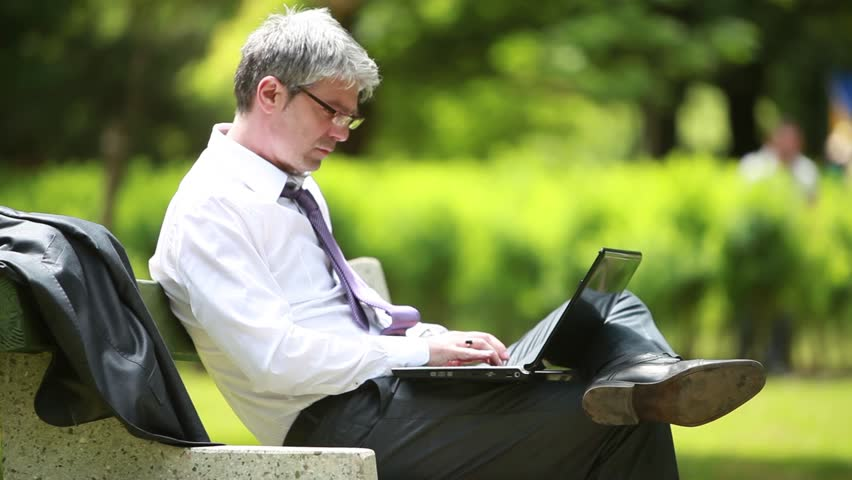 A young, handsome and self-confident businessman sitting on a bench in a park and using laptop