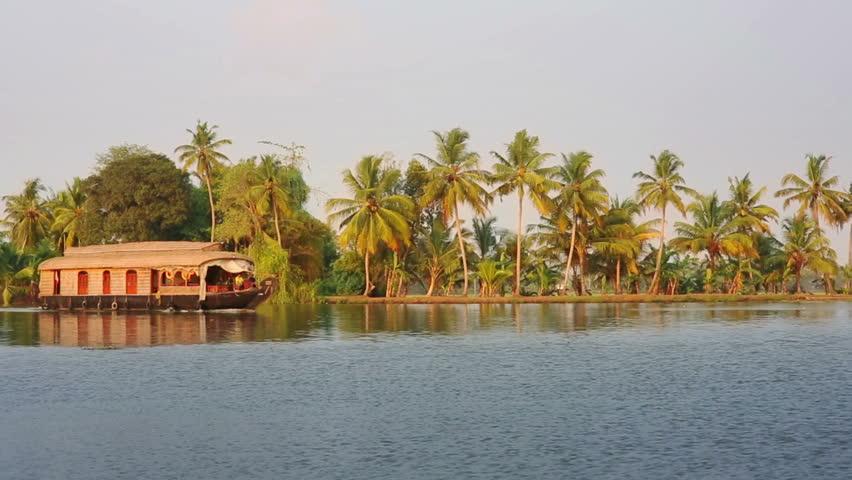 Traditional house boat moving along canal in Kerala Backwaters