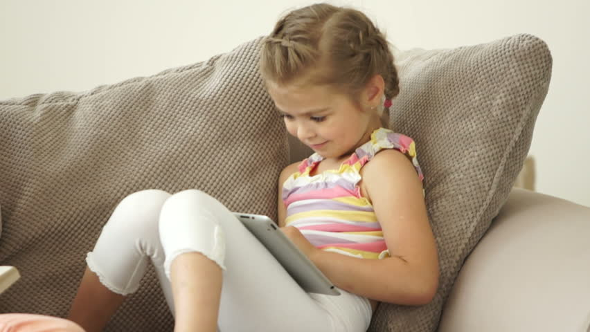 Two sisters sitting on sofa with book and tablet pc