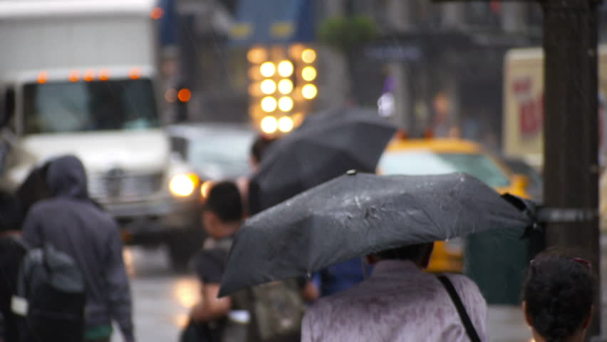 NEW YORK CITY, Circa June, 2013 - Pedestrians with umbrellas try to avoid