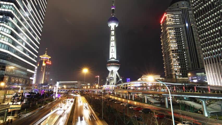 Shanghai landmark and city traffic at night - Shanghai, China. (tilt up)