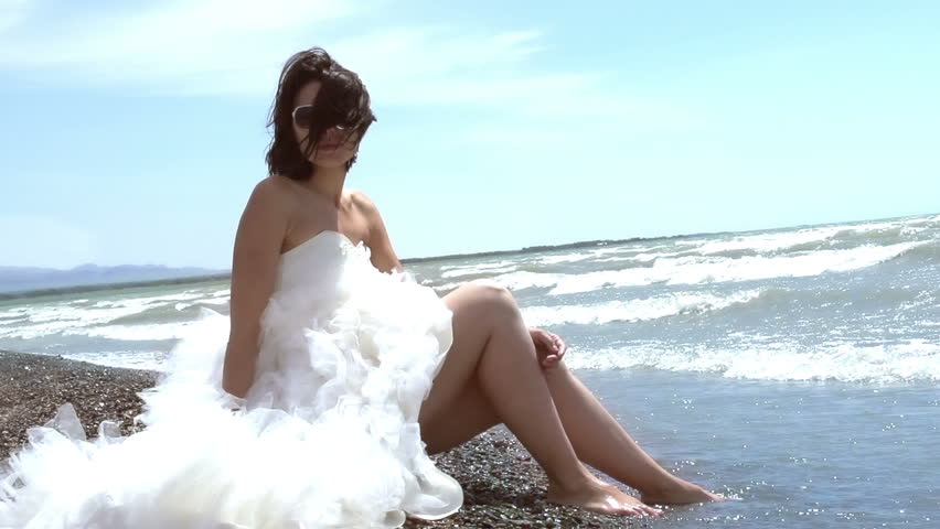 Perfect Honeymoon. Beautiful brunette in a wedding dress sitting by the sea. Rolling waves touch the feet. Slow Motion at a rate of 240 fps