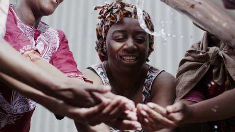 Happy villagers from a poor African community hold out their hands to receive a flowing stream of clear, fresh water. In slow motion.