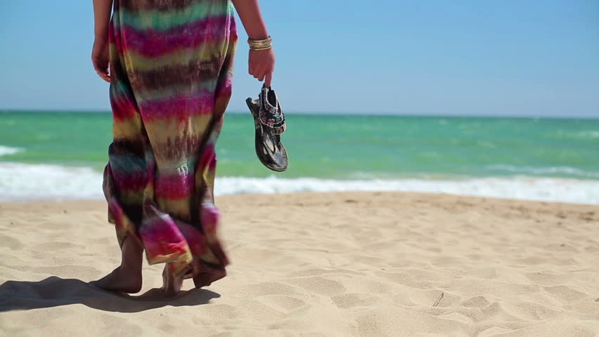 Woman with sandals standing on beautiful beach