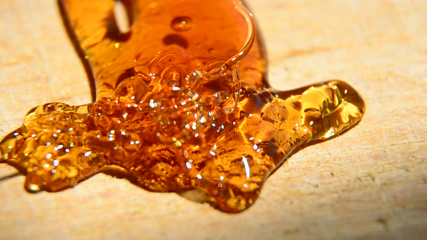 Pouring Golden Organic Honey and forming abstract arrow on wooden surface