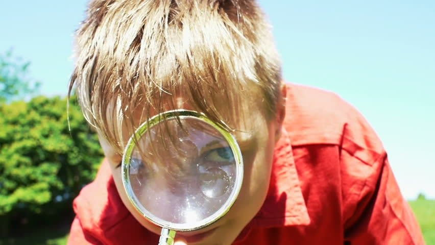 Young boy looking through magnifying glass toward the camera