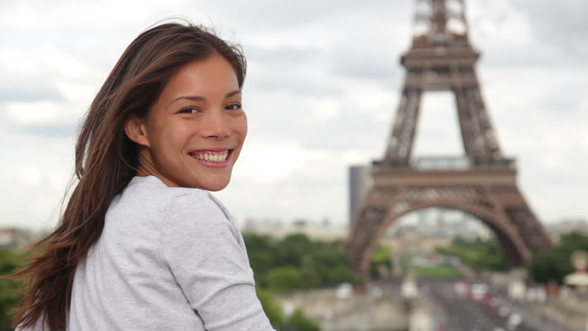 Eiffel Tower tourist in Paris smiling and looking at Eiffel Tower. Travel and tourism concept from Pairs, France with beautiful smiling young woman. Asian Caucasian mixed race female model.