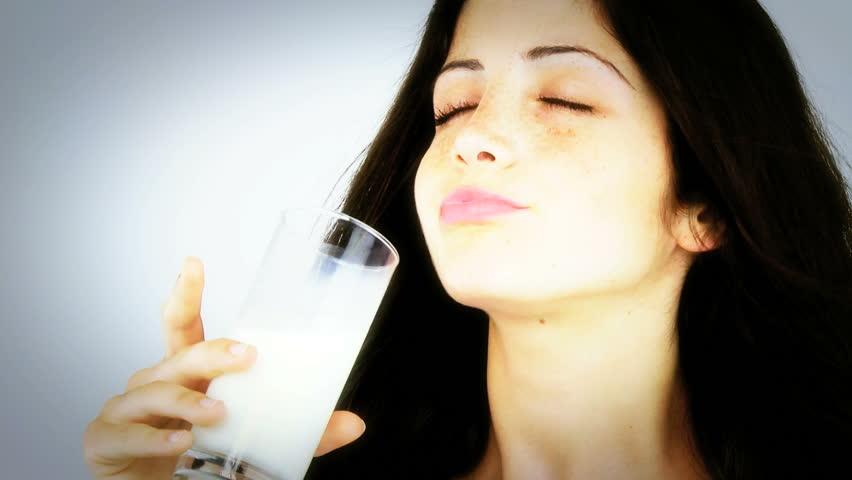 Woman enjoying fresh glass of milk isolated closeup