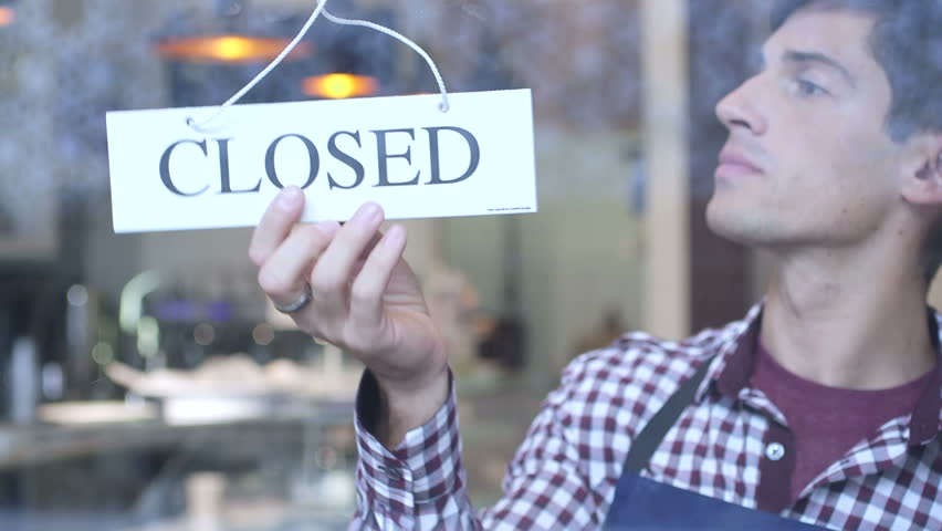 Man flipping over cafe closed sign