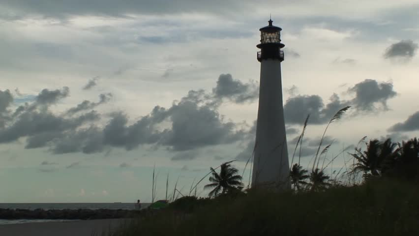 Biscayne Bay lighthouse on a beautiful day, surrounded by palm trees and blue sky