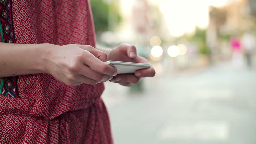 Female hands texting on smartphone in the city