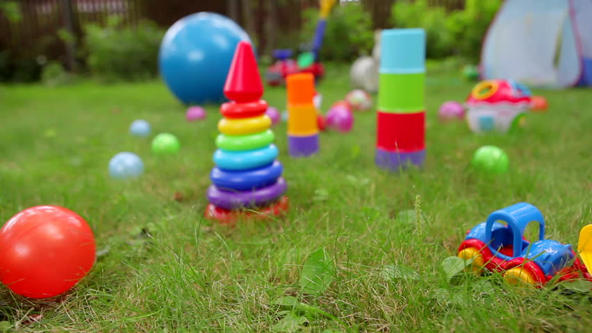 Toys On Grass And Unrecognizable Baby On Background (dolly ...