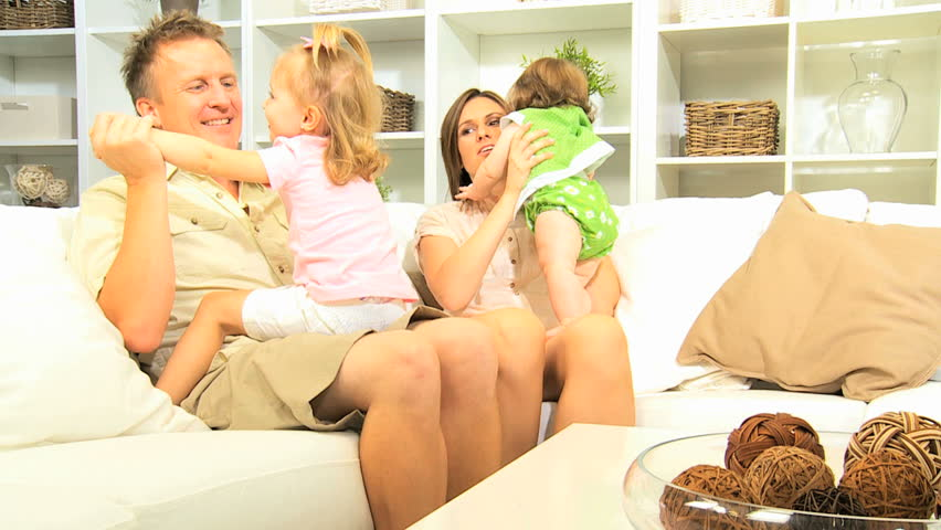 Laughing young Caucasian couple having fun with their little daughters sitting home   Shutterstock HD Video #4288226