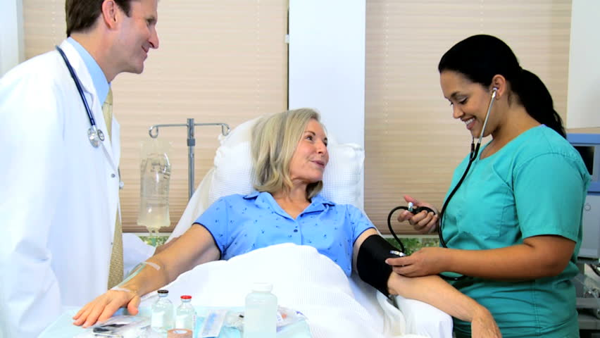 Latin American nursing aide taking the blood pressure of retired female patient #4312586