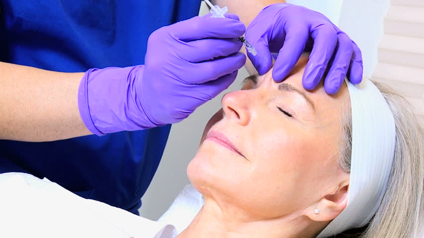 Male cosmetic surgeon performing non surgical facial treatments retired Caucasian female
