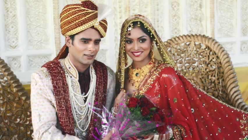 Pan shot of Indian bride and groom posing with holding a bouquet of flowers