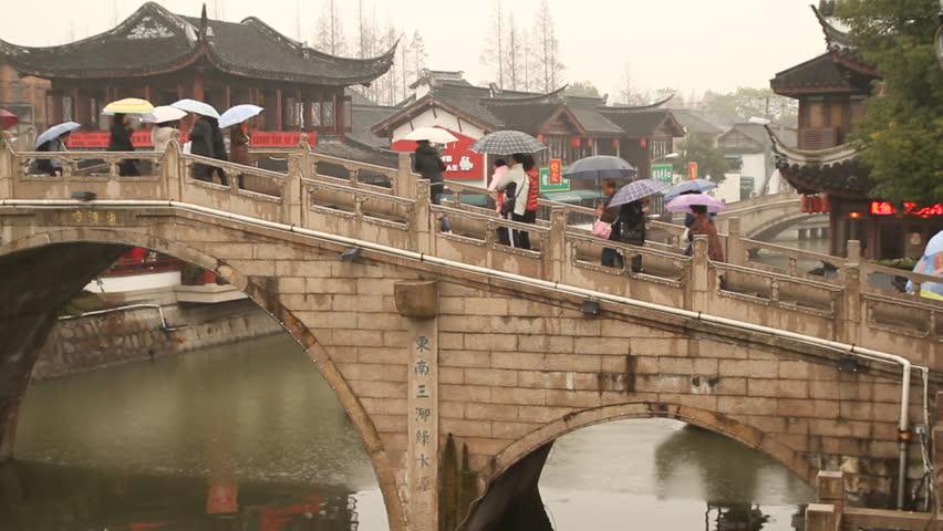 SHANGHAI - DECEMBER 16: Qibao Ancient Town stone arch bridge and boat on rainy