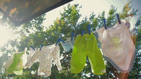 baby clothes hanging on a rope and drying