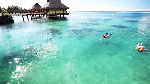 Young couple snorkeling in clean water next to resort