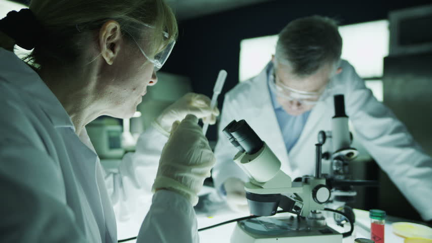 Mature male and female scientists or researchers working together in a dark laboratory, carrying out experiments with chemicals and microscope. In slow motion. | Shutterstock HD Video #4362068
