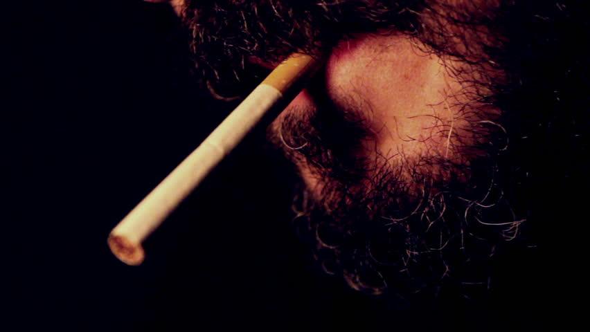 Man smoking a cigarette, close up on black
