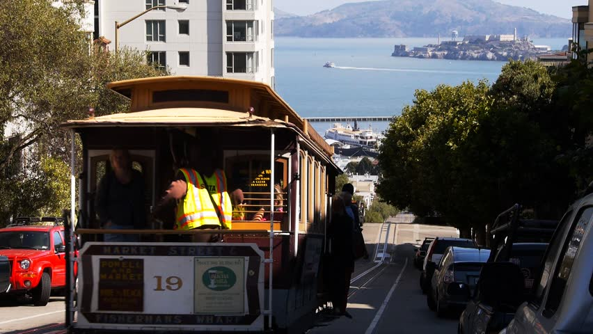 a san francisco cable car with alcatraz island in the background