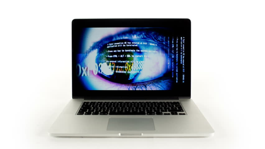 A laptop computer with a technology screensaver playing. the screen saver is an eye with data running over it and is work from my own collection