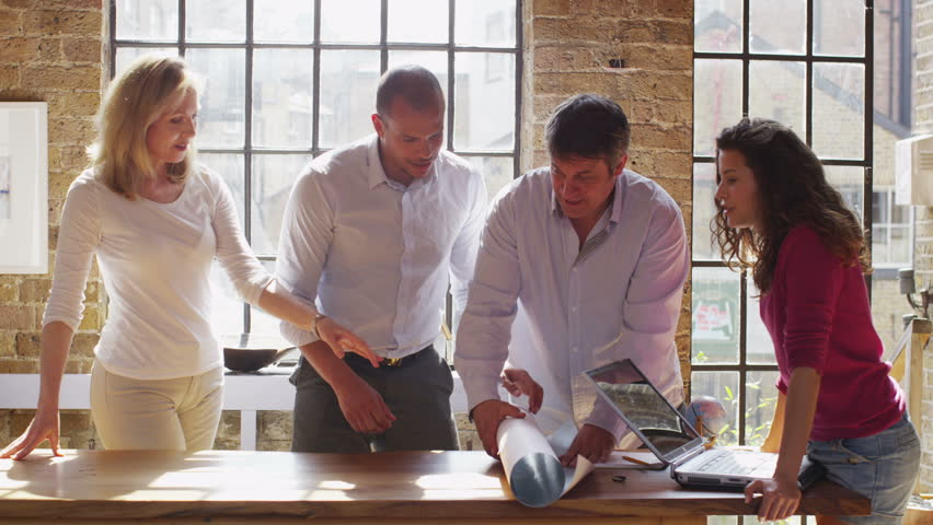Friends or casual business group working on a project, looking at world map in a light, natural setting. | Shutterstock HD Video #4387775